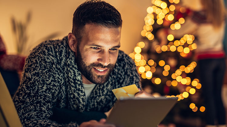 man shopping on tablet during holidays