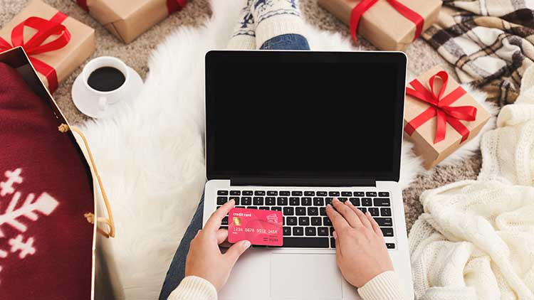 person christmas shopping on computer with credit card