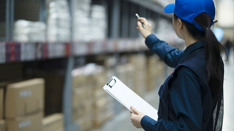woman in warehouse with clipboard