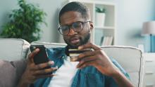 man shopping on phone with credit card out